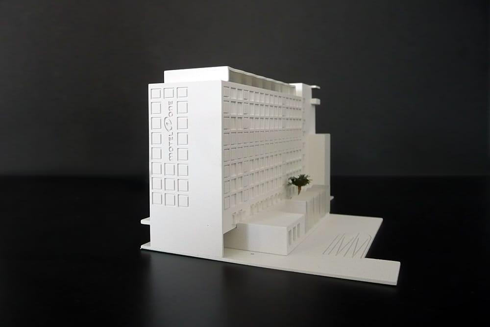 Wettbewerbsmodell eines Motel One Gebäudes im Maßstab 1:500, aus Kunststoff, mattweiß lackiert, vor einem schwarzen Hintergrund, entworfen für Landes und Partner.